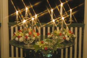 Decoración de las mesas de un evento con velas, candelabros y otras combinaciones